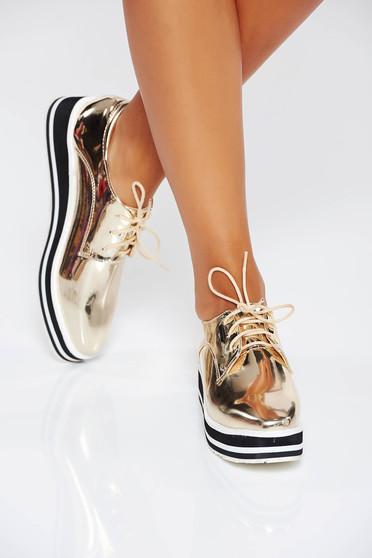 Hétköznapi fémes jellegu arany fűzővel köthető meg cipő